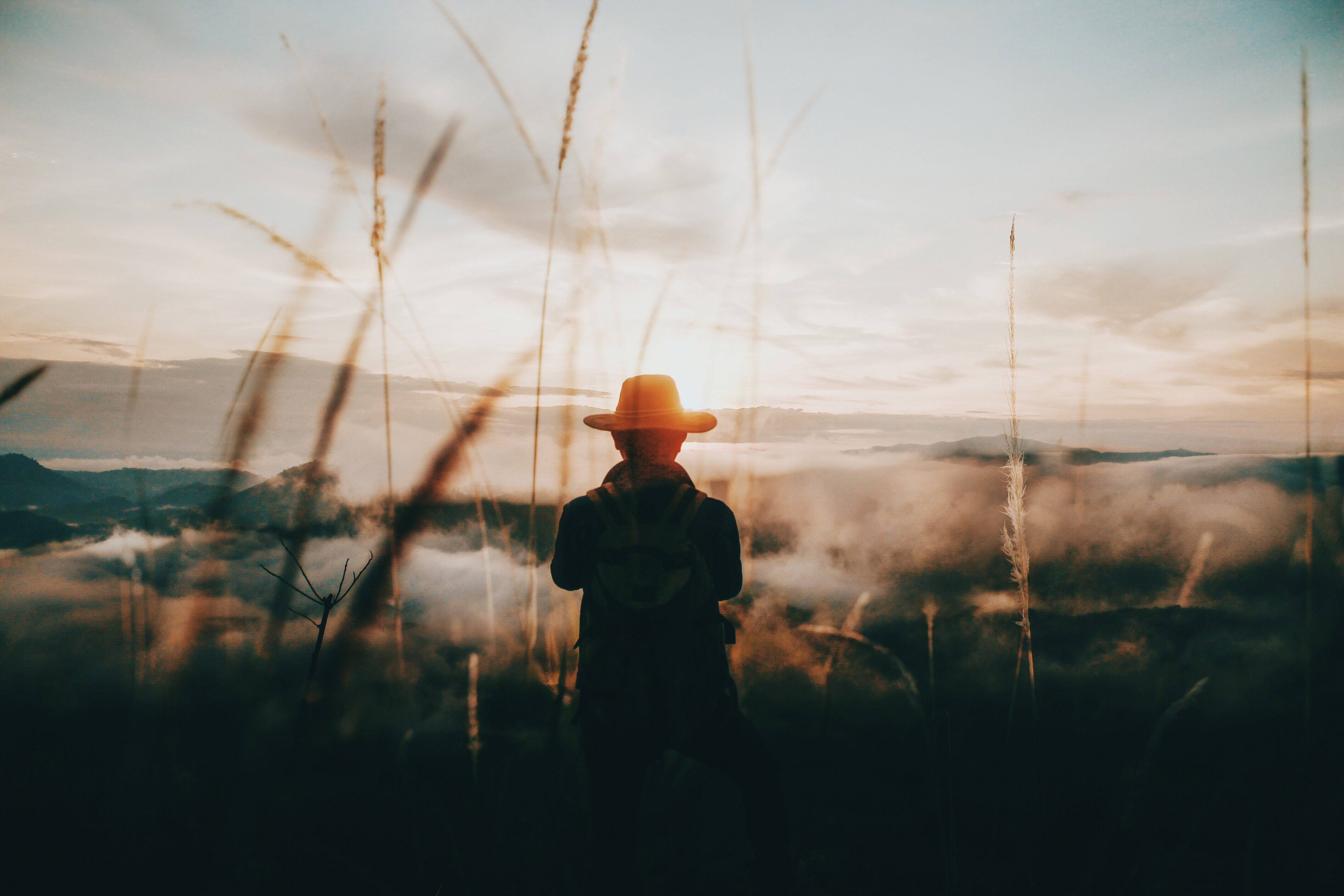 silhouette person red hat onlooking sunset