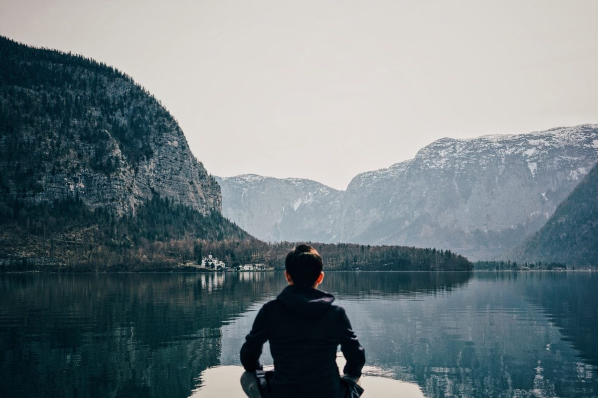 person meditating on a dock